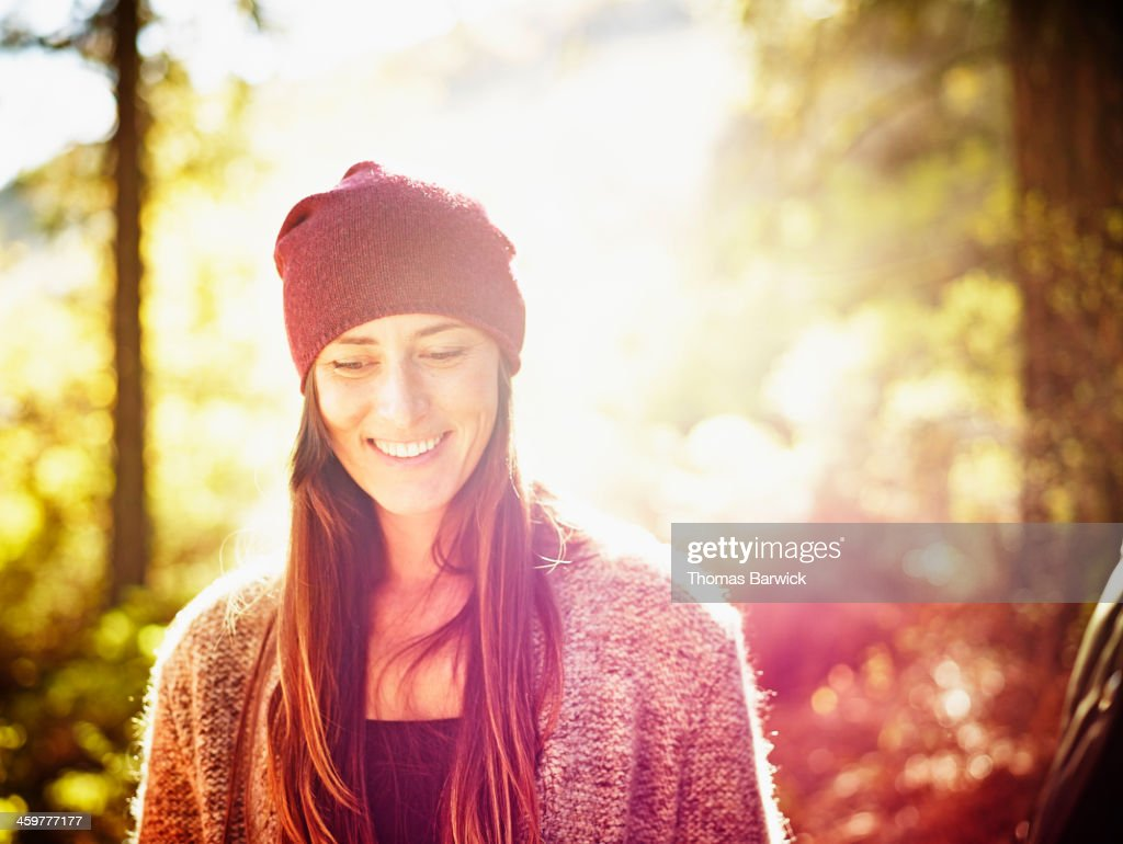 Smiling Woman Standing On Hillside In Forest ...