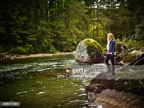 Smiling woman standing on rock near river : Stock Photo