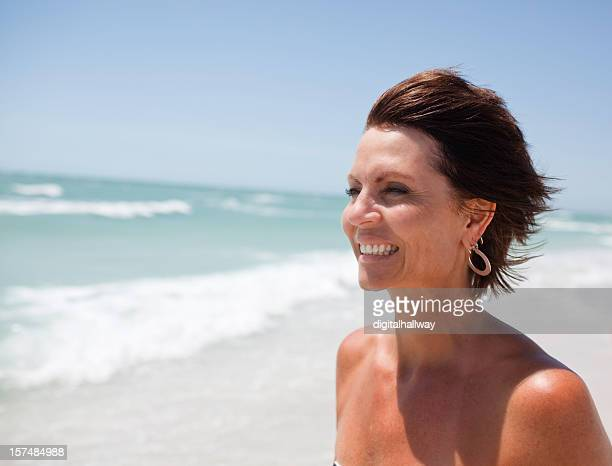Smiling woman standing on the shores of a wavy beach