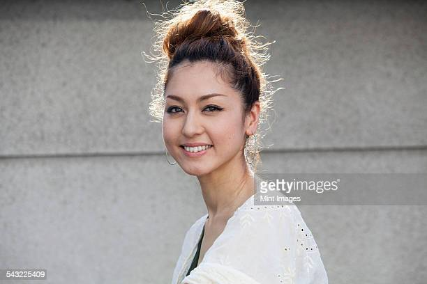 A smiling woman standing outdoors.