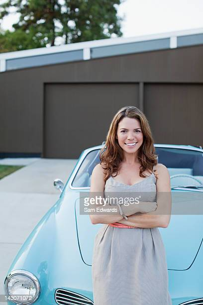 Smiling woman standing with convertible