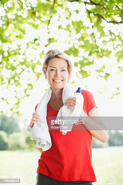 Smiling woman standing with towel and water bottle