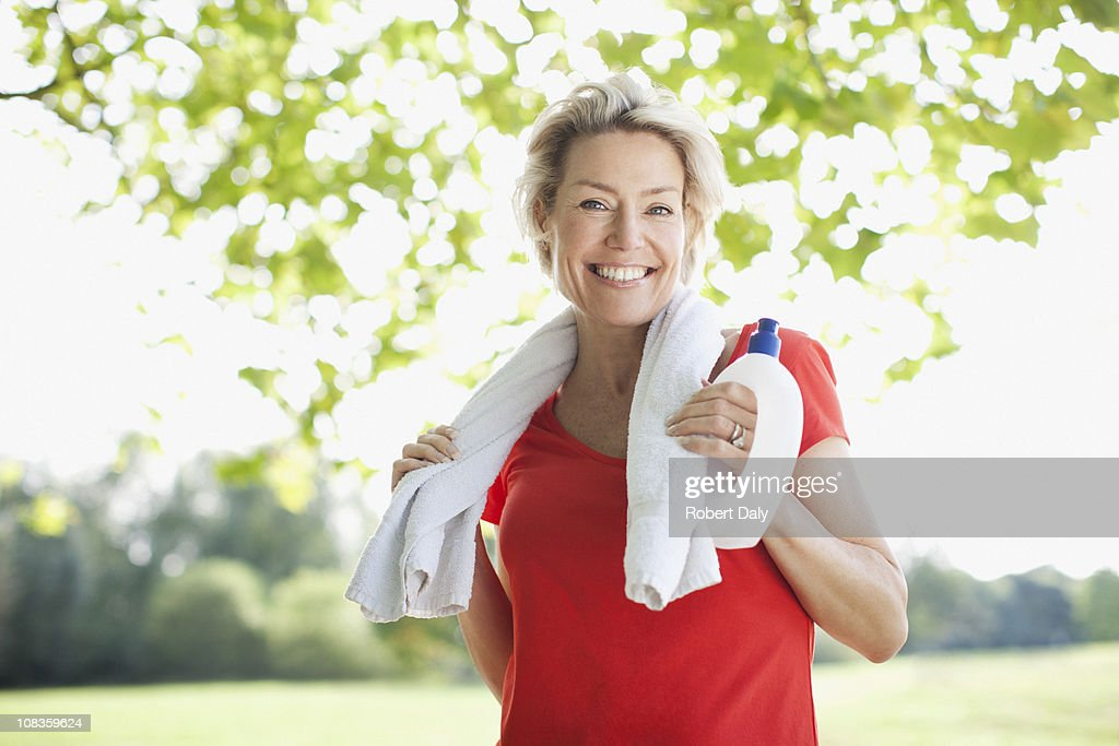 Smiling Woman Standing With Water Bottle And Towel Stock ...