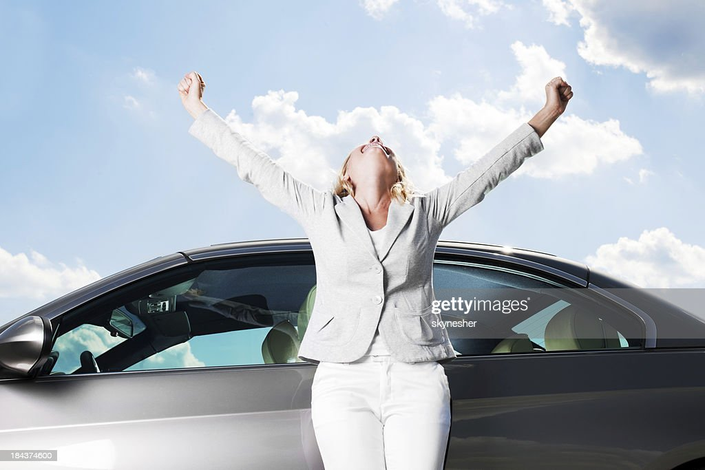 Smiling woman stretches arms toward sky in victory : Stock Photo