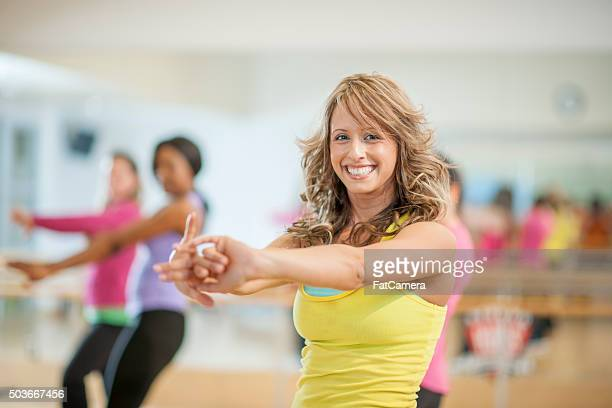 Smiling Woman Stretching in Class