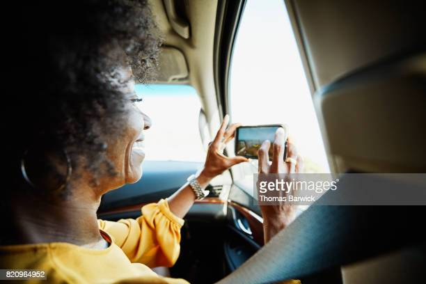 Smiling woman taking photo out car window with smartphone