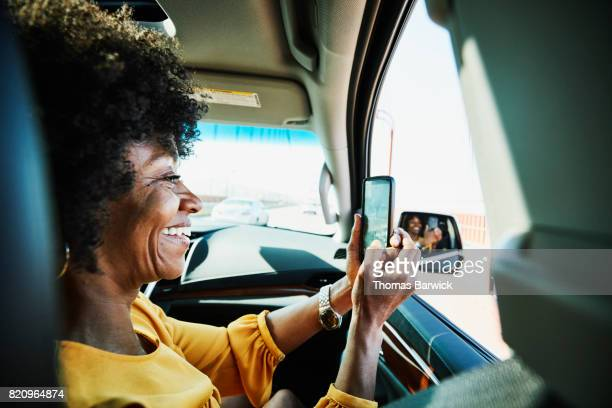 Smiling woman taking photo with smartphone out window of car