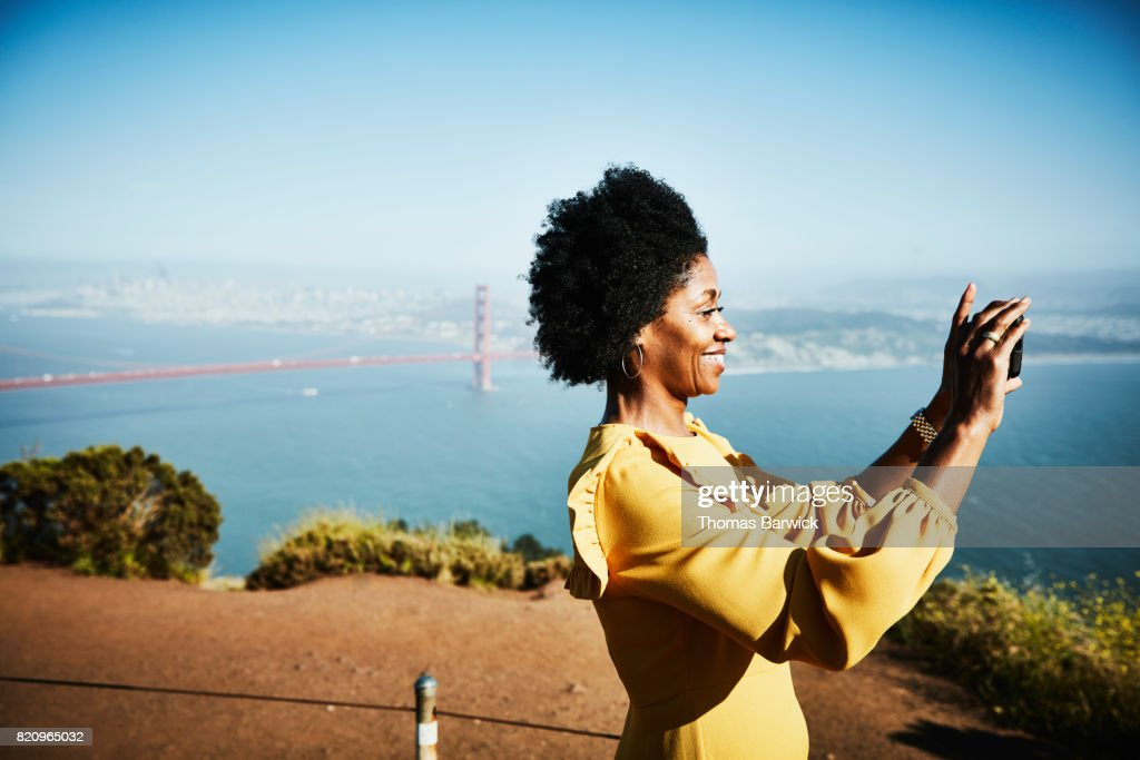 Smiling woman taking photo with smartphone while standing at vista above San Francisco : Stock Photo