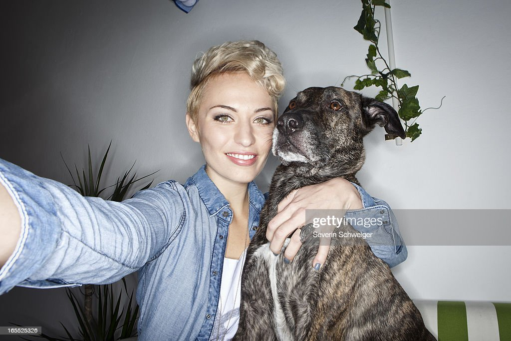Smiling woman taking picture with dog