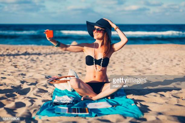 Smiling woman taking selfie at the beach