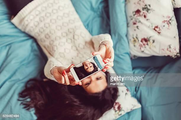 Lächelnde Frau ein selfie aufnehmen im Bett