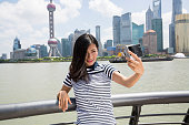 Smiling woman taking selfie while standing by railing against Pudong skyline