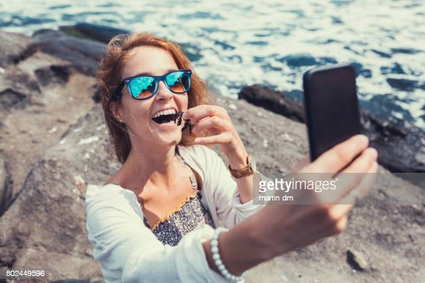 Smiling woman taking selfie with little crab