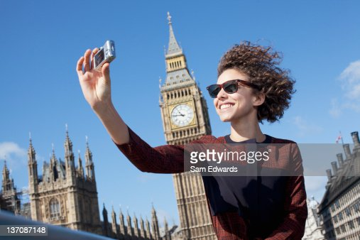 Smiling woman taking self-portrait with digital camera below Big Ben clocktower