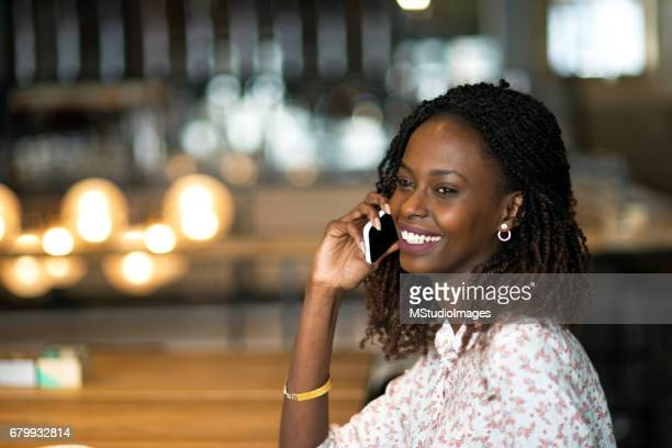 Smiling woman talking on mobile phone.