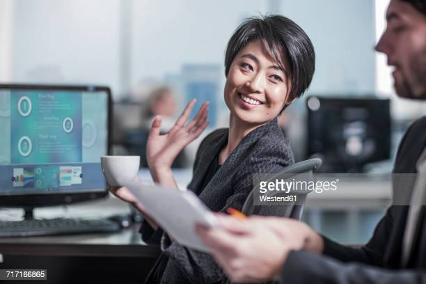 Smiling woman talking to colleauge in city office