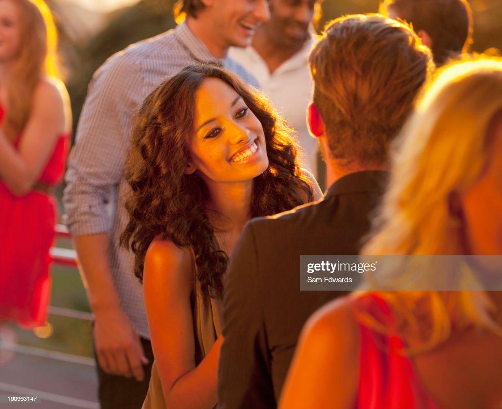 Smiling woman talking to man on sunny balcony : Stock Photo