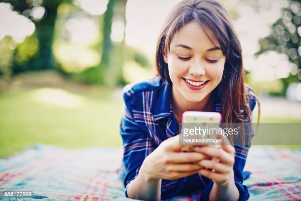Smiling woman text messaging on smartphone while relaxing in park