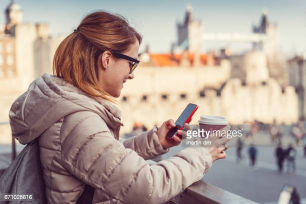 Smiling woman texting in London