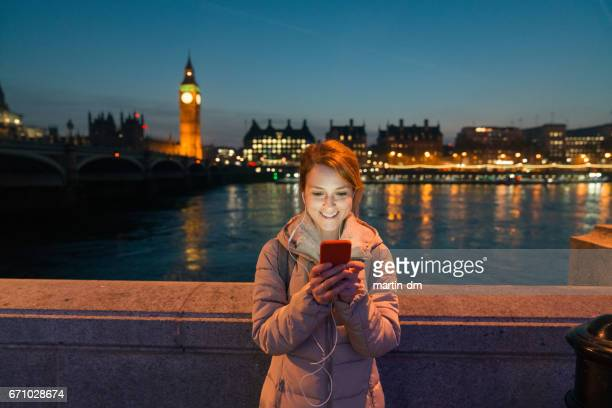 Smiling woman texting near the Thames river