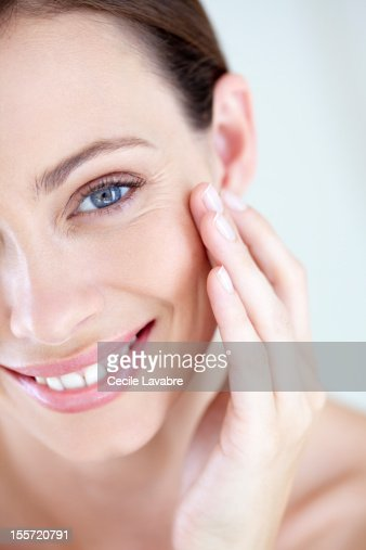 A smiling woman touching her face