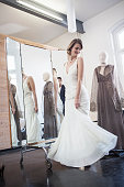 Smiling woman trying on gown