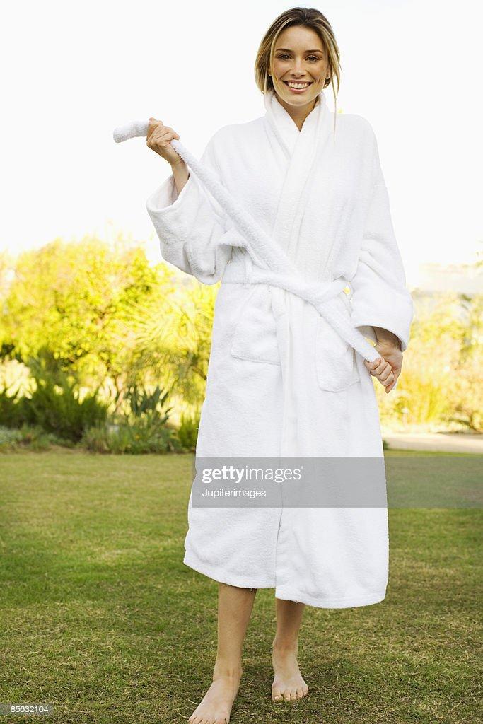 Smiling woman tying bathrobe