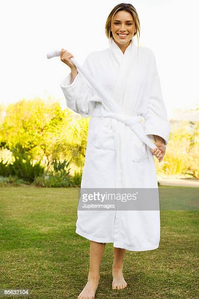 Smiling woman tying bathrobe