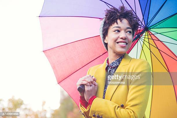 Smiling woman under colorful umbrella (London, UK)