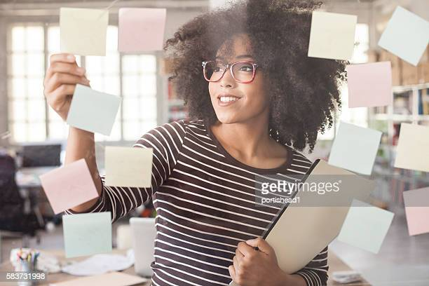 Smiling woman using adhesive notes in modern office