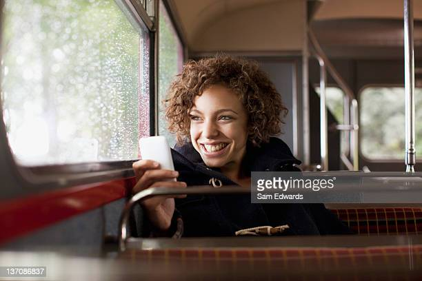 Smiling woman using cell phone on bus