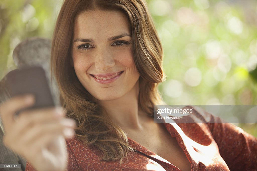 Smiling woman using cell phone outdoors : Stock Photo