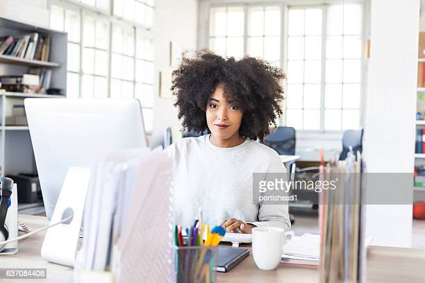 Smiling woman using computer in modern workplace