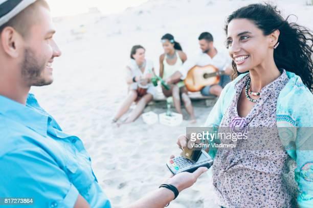 Mujer sonriente con tarjeta de crédito en la playa