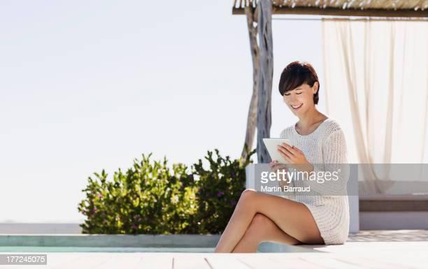 Smiling woman using digital tablet at poolside