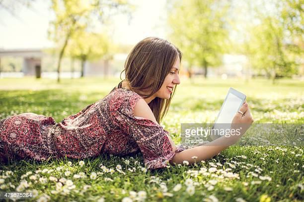 Femme souriante avec agenda électronique sur le parc.