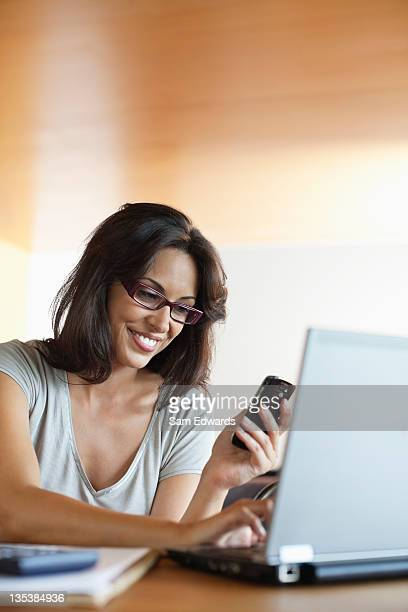 Smiling woman using laptop and cell phone