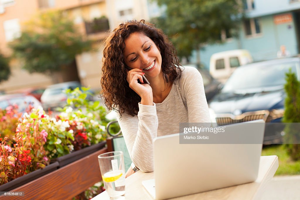 Smiling woman using laptop and talking on the phone : Stock Photo