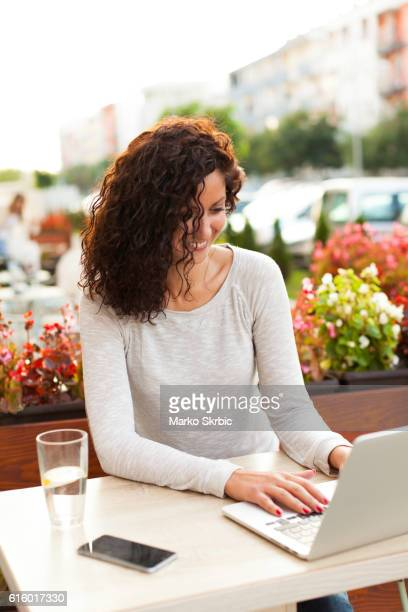 Smiling woman using laptop in coffee shop