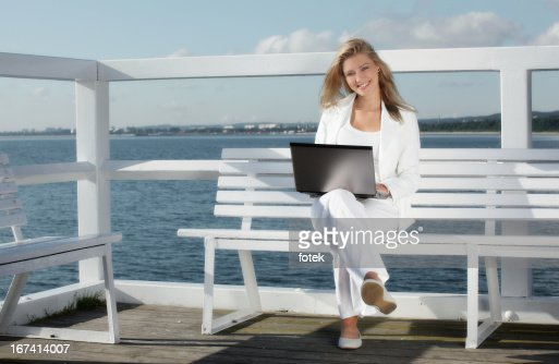 Smiling woman using laptop outdoors : Bildbanksbilder