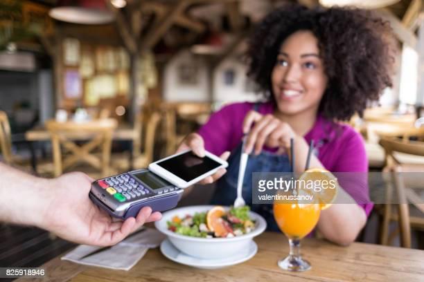 Lächelnde Frau mit mobile-Payment in restaurant