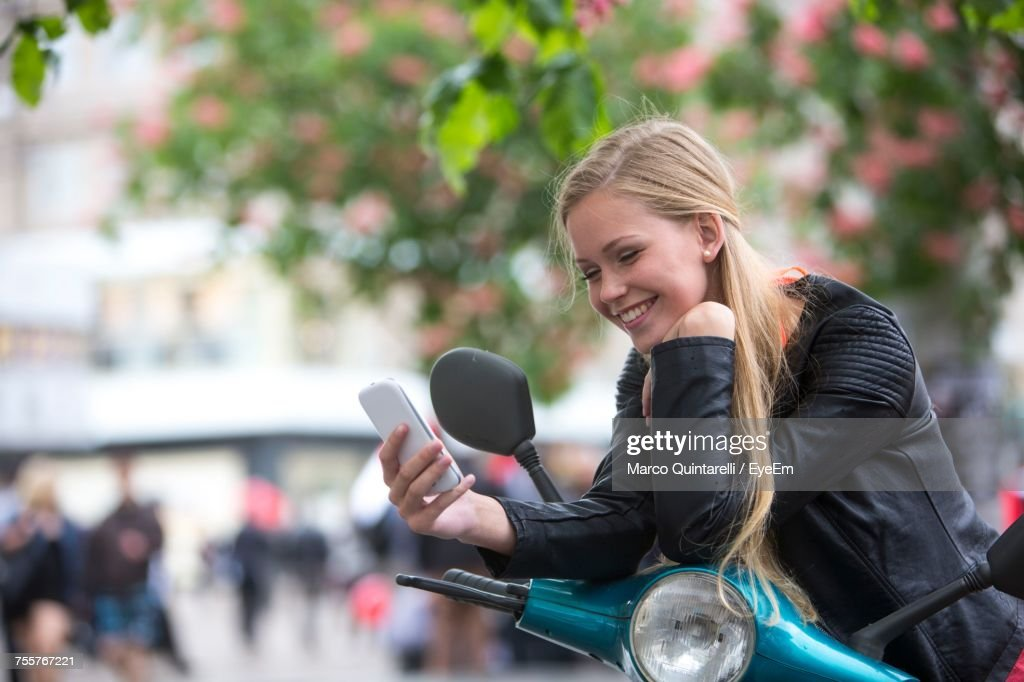 Smiling Woman Using Mobile Phone While Leaning On Motor Scooter : Stock Photo