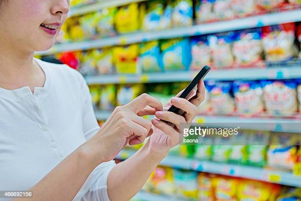 Smiling woman using smartphone in the supermarket