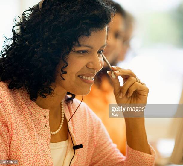Smiling Woman Using Telephone Headset