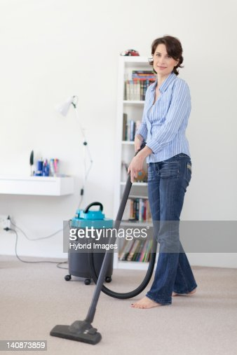 Smiling woman vacuuming living room : Stock-Foto