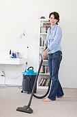 Smiling woman vacuuming living room
