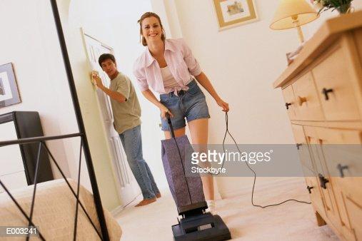Smiling woman vacuuming, man dusting : Stock Photo