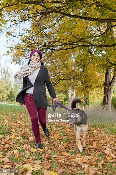 Smiling woman walking dog in park