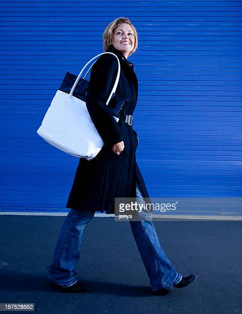 smiling woman walking down the street carrying hand bag