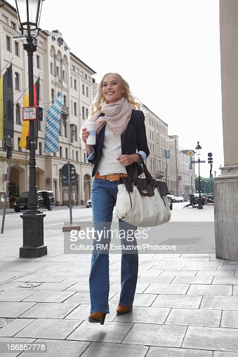 Smiling woman walking on city street